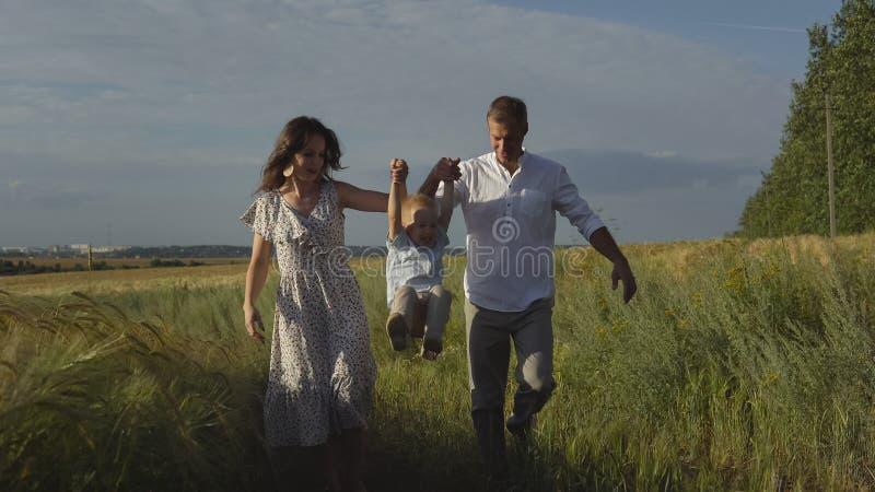 Familj som går på ängen, föräldrar som spelar med sonen royaltyfria foton
