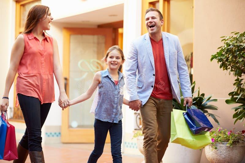 Familj som går till och med galleria med shoppingpåsar fotografering för bildbyråer