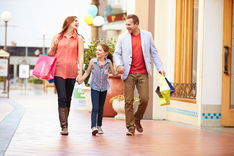 Familj som går till och med galleria med shoppingpåsar arkivbilder