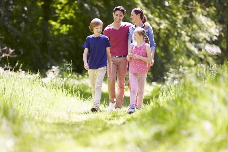 Familj som går till och med sommarbygd arkivfoto