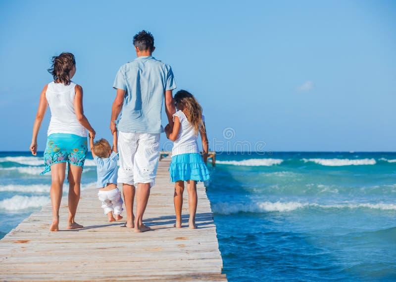 Familj som går träbryggan royaltyfria foton