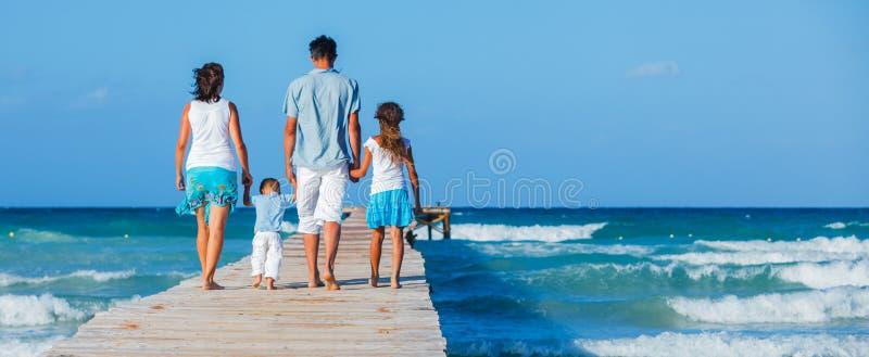 Familj som går träbryggan royaltyfri fotografi