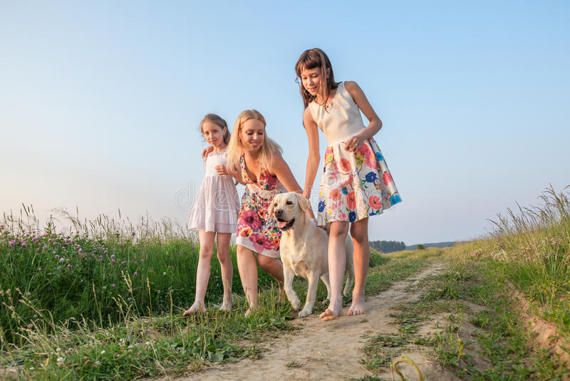 Familj som går whithhunden arkivfoto