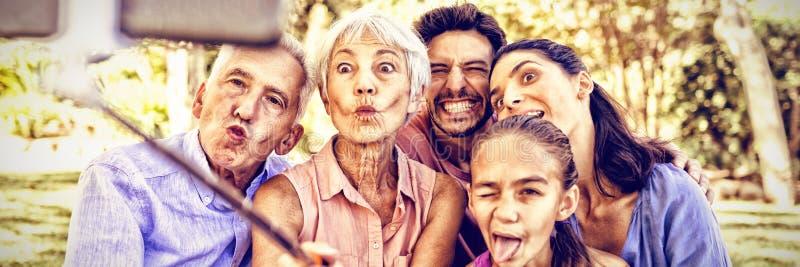 Familj som gör roliga framsidor, medan ta en selfie i parkera arkivfoto