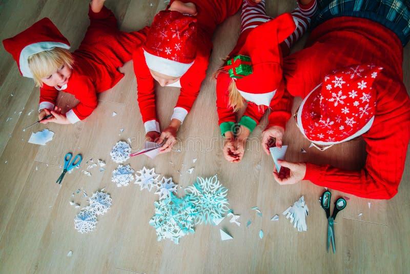 Familj som gör snöflingor från papper, julhantverk royaltyfria foton