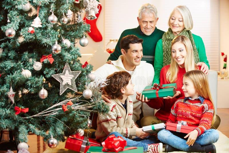 Familj som ger gåvor på jul arkivfoton