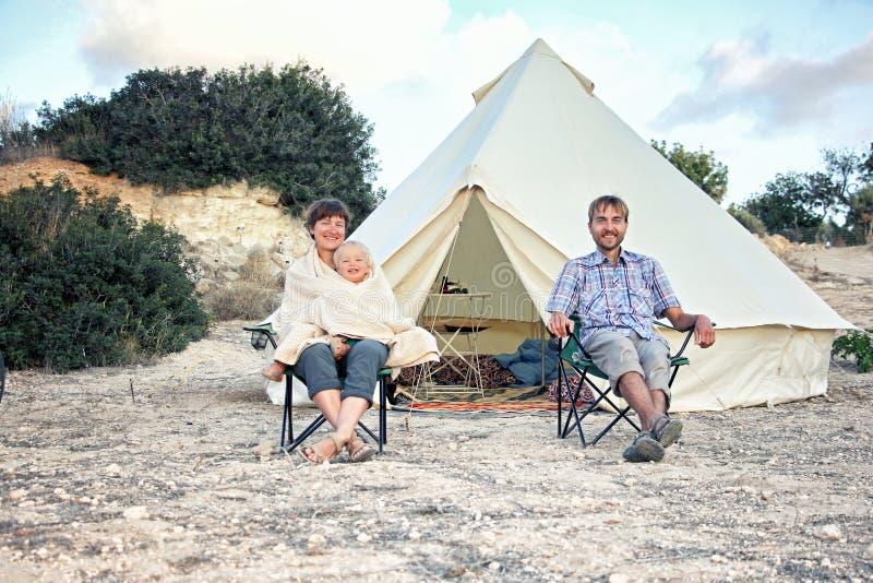 Familj som glamping utomhus- semester Moder-, fader- och litet barnson som sitter nära det stora retro campa tältet med den hemtr arkivfoton