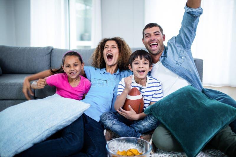 Familj som håller ögonen på den amerikanska fotbollsmatchen på television arkivfoton
