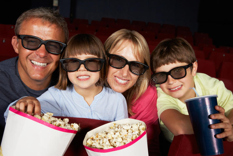 Familj som håller ögonen på filmen 3D i bio royaltyfri bild