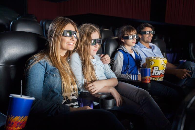 Familj som håller ögonen på filmen 3D i teater arkivfoto