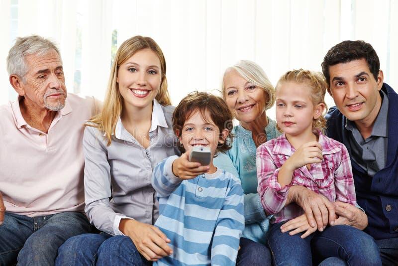 Familj som håller ögonen på smart TV med fjärrkontroll royaltyfri foto