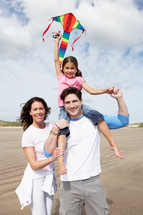 Familj som har den roliga flygdraken på strandferie royaltyfri bild
