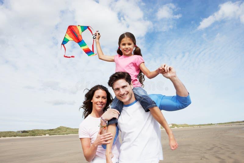 Familj som har den roliga flygdraken på strandferie arkivbild