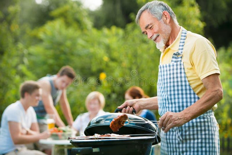 Familj som har en grillfestdeltagare arkivfoton