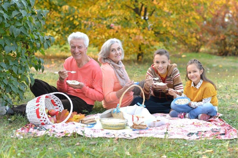 Familj som har en picknick i parkera i höst royaltyfri foto