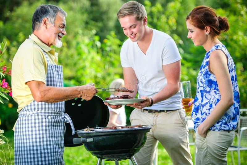 Familj som har ett grillfestparti royaltyfria bilder