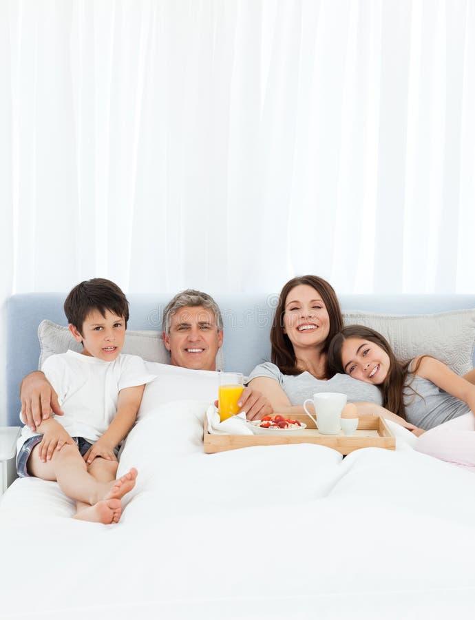 Familj som har frukosten i deras underlag arkivfoto
