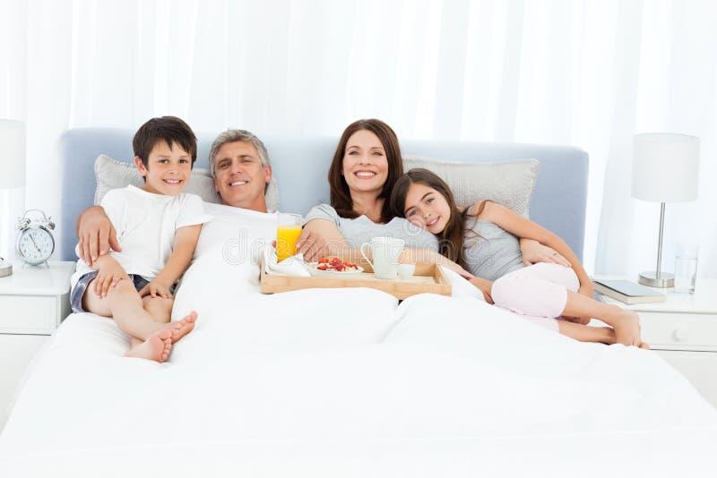 Familj som har frukosten i deras underlag arkivbild