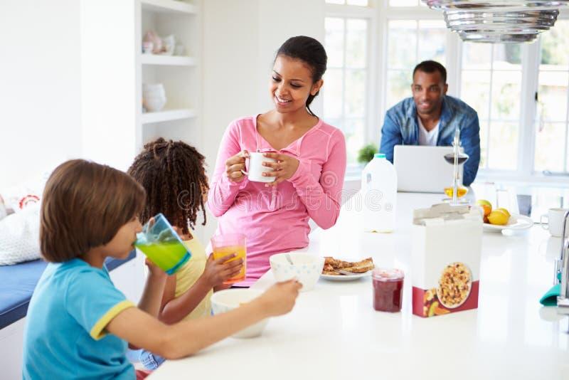 Familj som har frukosten i kök tillsammans arkivbilder