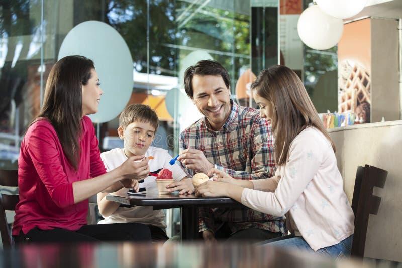 Familj som har glassar på tabellen i mottagningsrum royaltyfri bild