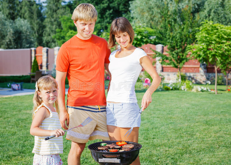 Familj som har grillfesten fotografering för bildbyråer