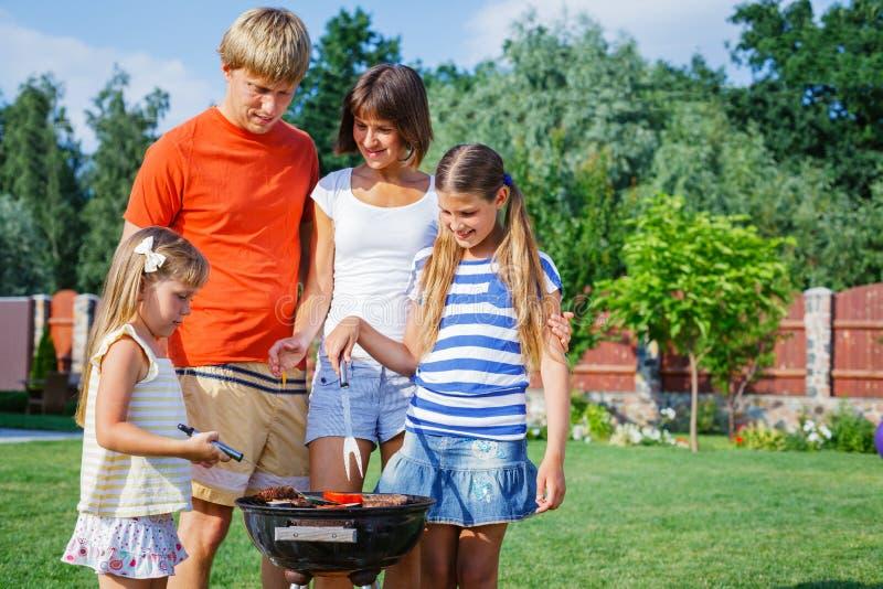 Familj som har grillfesten arkivbild