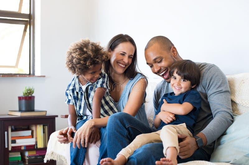 Familj som har gyckel hemma arkivbilder