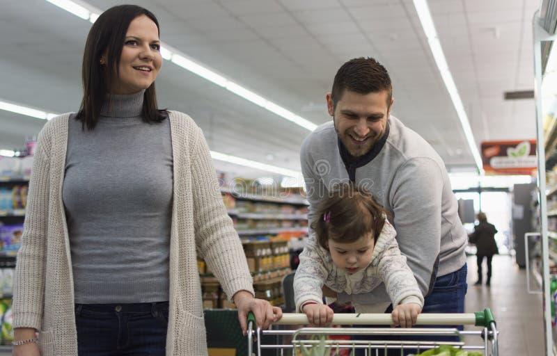 Familj som har gyckel i supermarket arkivfoton