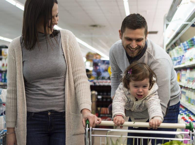 Familj som har gyckel i supermarket arkivfoto