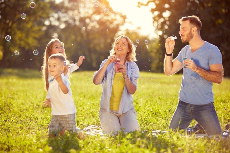 Familj som har gyckel med såpbubblor royaltyfria bilder