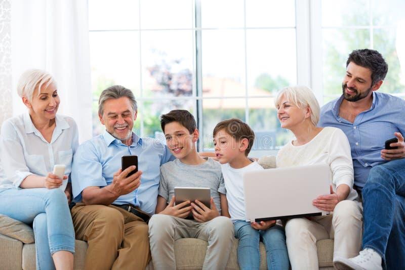 Familj som har gyckel med teknologi royaltyfri foto