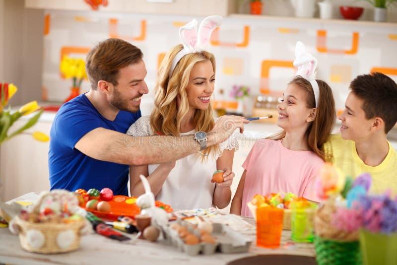 Familj som har gyckel, medan måla påskägg arkivbilder