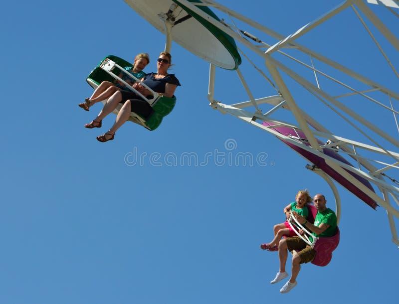 Familj som har gyckel på fallskärmsjägarenöjesplatsritten royaltyfria bilder