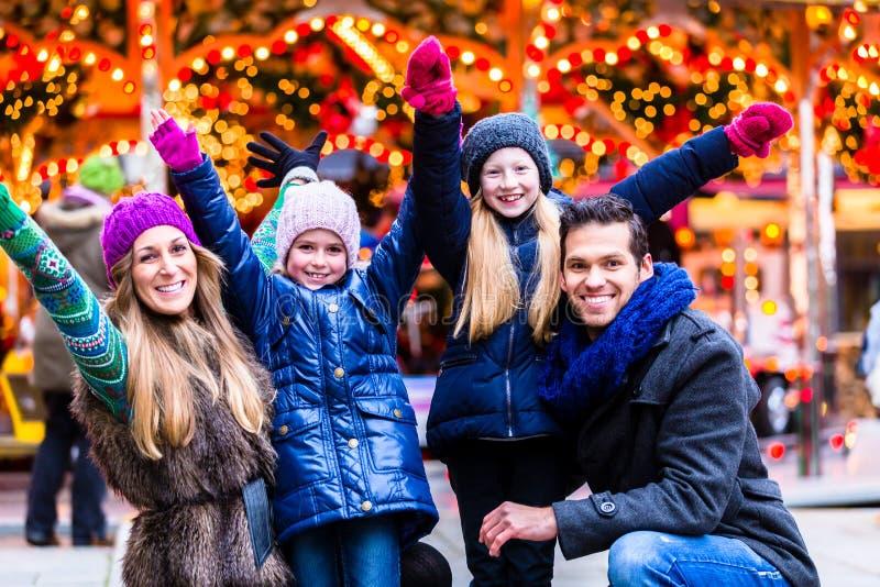 Familj som har gyckel på julmarknad royaltyfria bilder