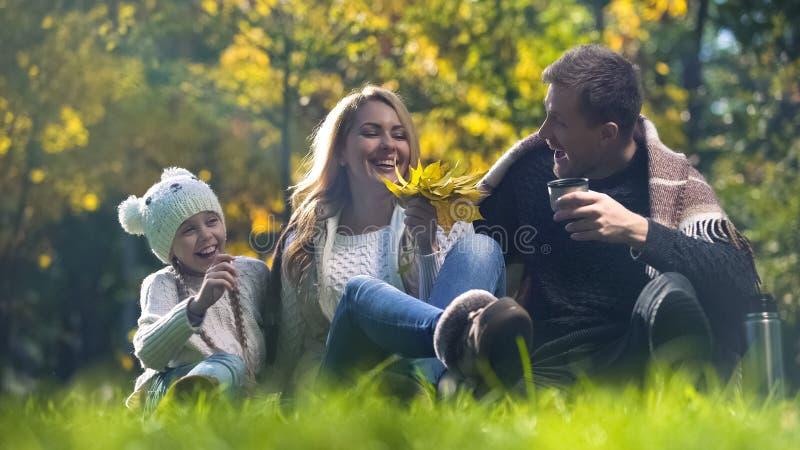 Familj som har gyckel på picknicken i höstskog, medvetet föräldraskap, wellbeing royaltyfri bild