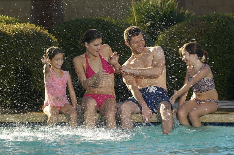 Familj som har gyckel på simbassängen royaltyfri foto