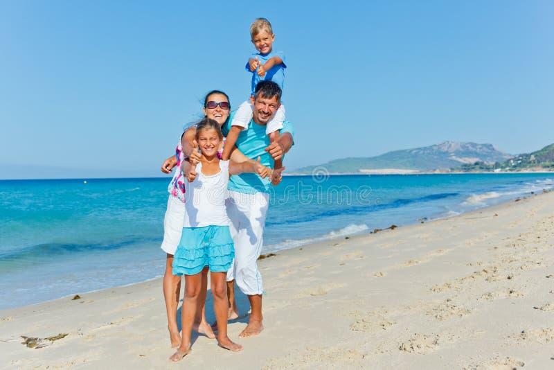 Familj som har gyckel på stranden arkivfoto