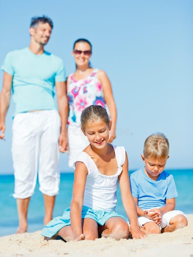 Familj som har gyckel på stranden royaltyfri bild