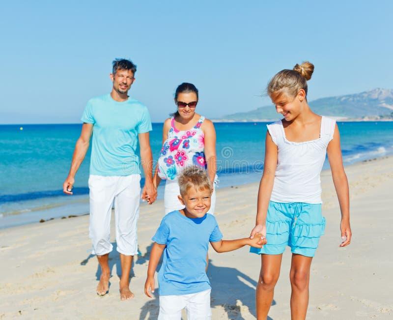 Familj som har gyckel på stranden royaltyfria foton