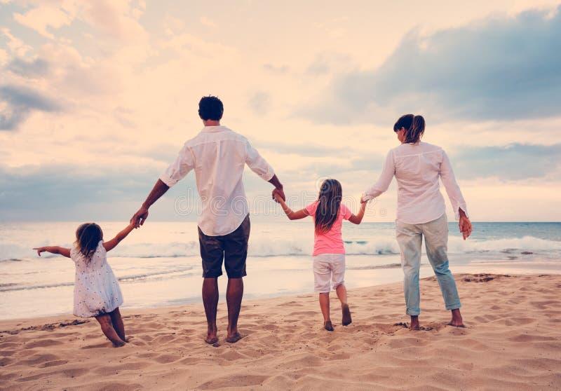 Familj som har gyckel på stranden på solnedgången arkivbild