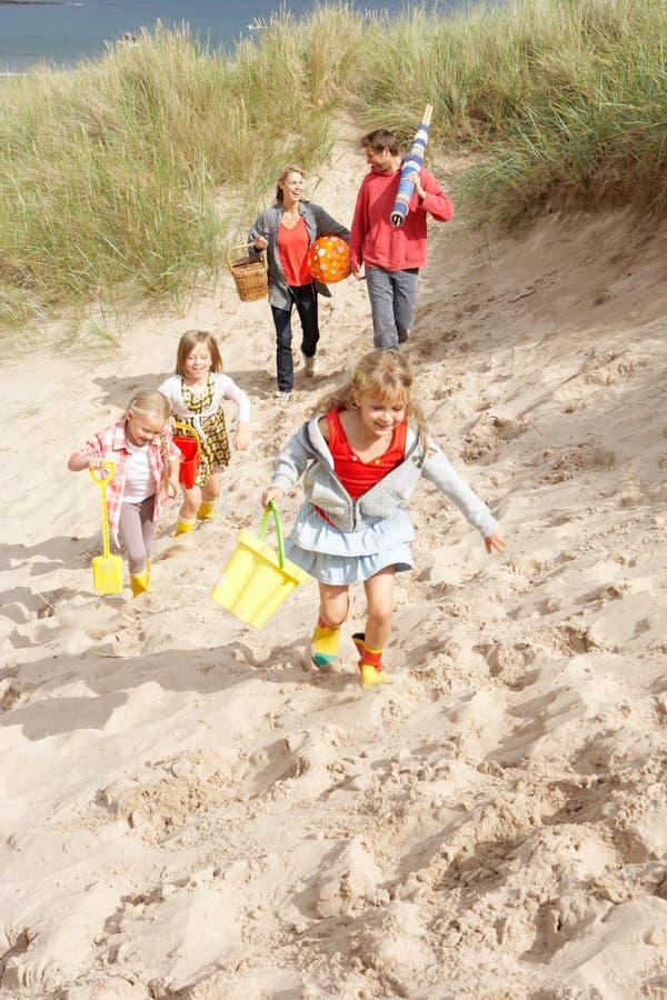 Familj som har gyckel på strandsemester arkivbilder