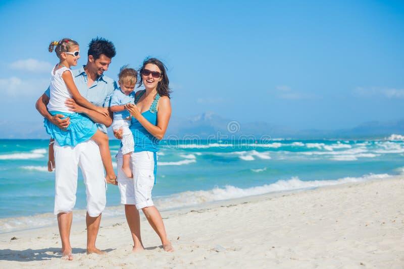 Familj som har gyckel på tropisk strand royaltyfri bild