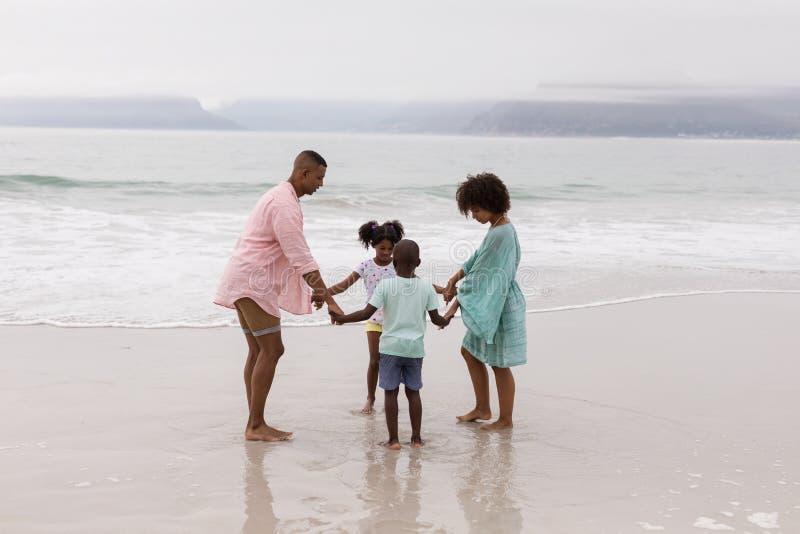 Familj som har gyckel p? stranden arkivfoton