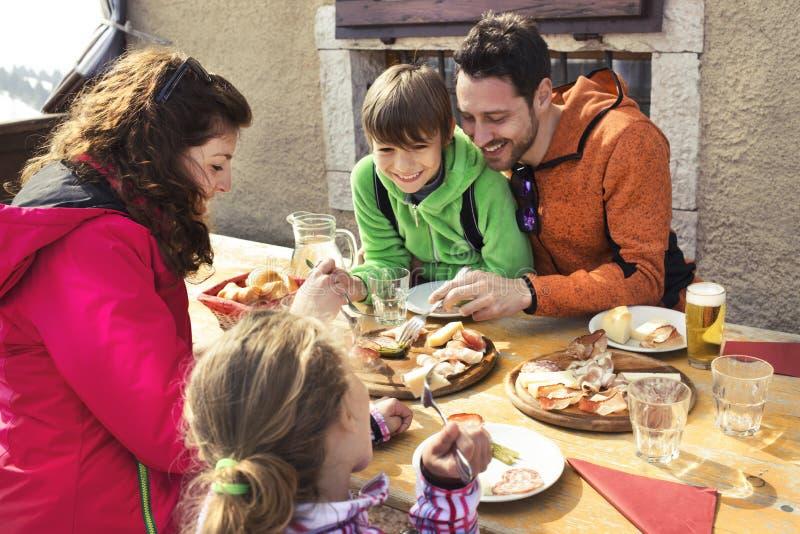 Familj som har lunch i en chalet i berg royaltyfria bilder