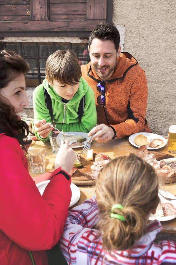 Familj som har lunch i en chalet i berg royaltyfria foton