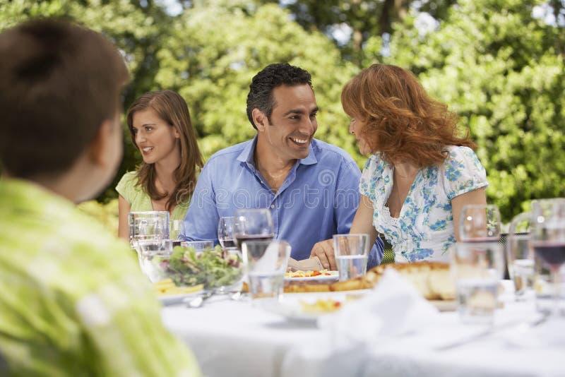 Familj som har lunch på tabellen i trädgård royaltyfria foton