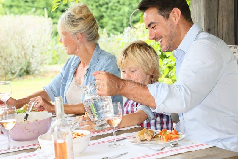 Familj som har lunch på terrass arkivbild