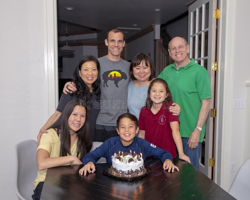 Familj som har rolig fira födelsedag för pojke` s med en glasskaka arkivfoton