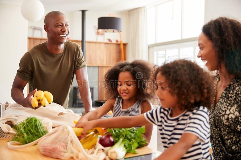 Familj som hem går tillbaka från shoppingturen som packar upp plast- fria livsmedelsbutikpåsar fotografering för bildbyråer