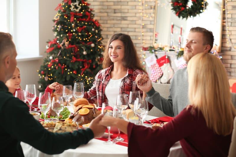 Familj som hemma ber innan att ha julmatställen fotografering för bildbyråer